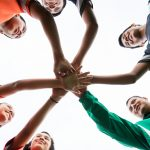 Group of people with their hands in the middle of a circle