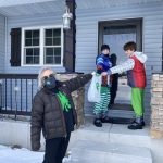 shows a 4-H educator in a mask delivering a bag of supplies to twin boys on a snowy door step